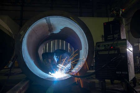 Welder performs welding work semi-automatic electric arc welding. Stainless steel pipe welding. Pipe production. MIG welding.