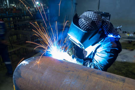 A welder performs semi-automatic arc welding at a manufacturing facility.