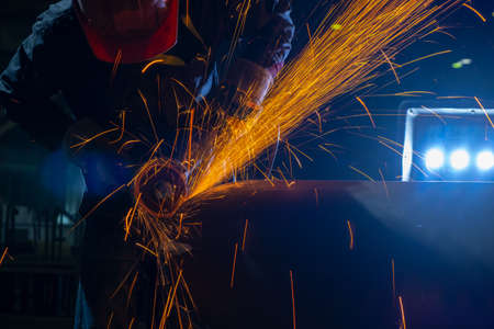 Production of pipes in the workshop of the plant. Sparks from an angle grinder