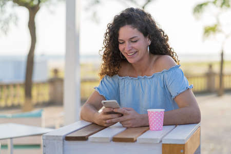 Beautiful young girl with green eyes sending messages with the mobile phone