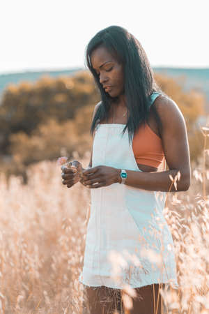 Pensive woman. Outdoor fashion photo of young beautiful black lady in autumn landscape with dry flowers. Warm Autumn
