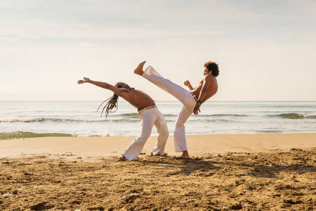 Capoeira team training on the beach - Martial arts athletes performing stunts
