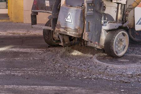 Asphalt milling machine working around sewer lid