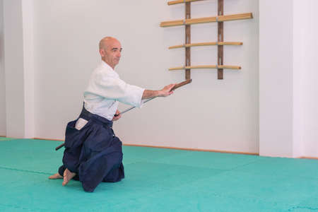 Aikido master practices defense posture. Healthy lifestyle and sports concept. Man in white kimono on white background. Karate man with concentrated face in uniform