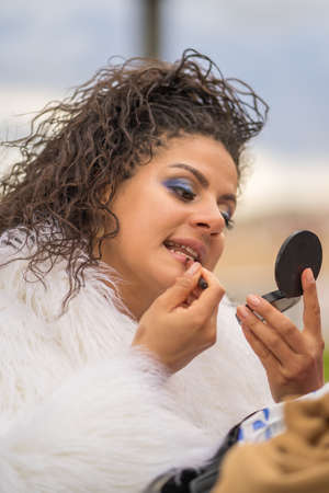 A beautiful young Caucasian woman doing make-up on the street