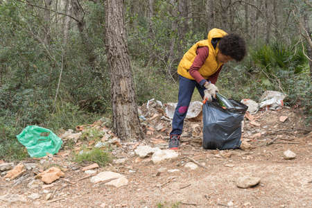 Black child picking up a glass bottle from the forest to recycle