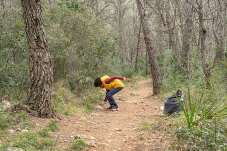 Black child picking up trash from the forest to recycle Stock Photo