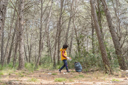 Black child picking up a plastic bottle from the forest to recycle Stock Photo - 121268283