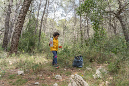 Black child picking up a plastic bottle from the forest to recycle Stock Photo