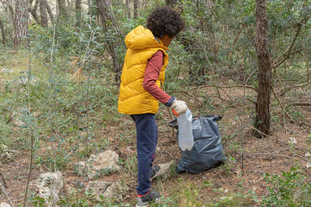 Black child picking up a plastic bottle from the forest to recycle 스톡 콘텐츠