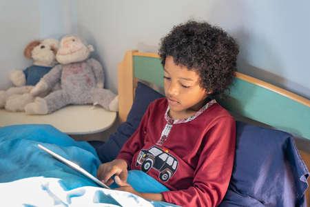 Happy black child using digital tablet in bed Reklamní fotografie
