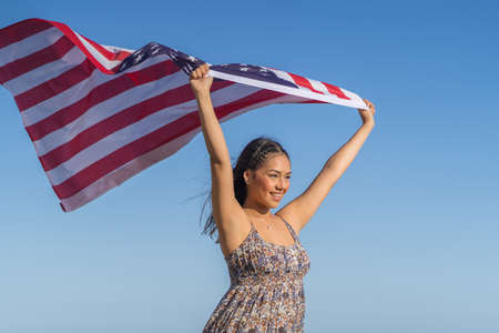 pretty and happy girl holds a American flag against the sky. July 4th Independence Day.