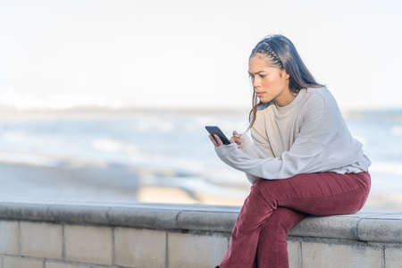 Latina girl is surprised after reading a message on her mobile phone at the seaside - technology and lifestyle concept