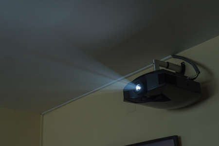 Projector in operation hanging from the living room wall. High definition projector