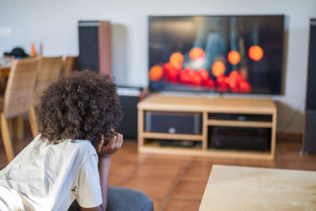 Little black boy watching cartoons on TV at home, back view. Rear view