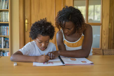 A mother helping her son to do the school homework. Stock Photo