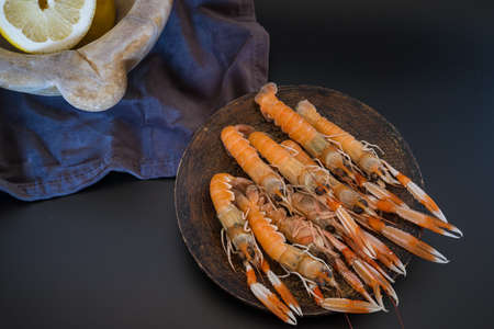 Delicious raw langoustines with a stone mortar full of lemons on dark background