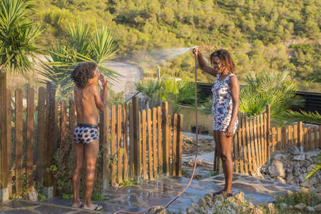 Black mother and his son playing in the garden with hose in summer. Lifestyle concept Stock Photo