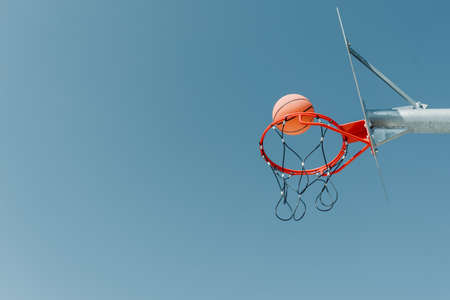 The ball flies toward the hoop on an outdoor basketball court in a public park. Copy space
