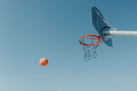 Metal street basketball board with hoop on outdoor court against blue sunny sky. Copy space Stock Photo