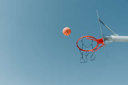 Ring and ball on background of the sky and the city.Basketball in Flight