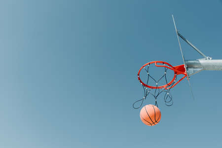 The ball flies into the hoop on an outdoor basketball court in a public park. Copy space