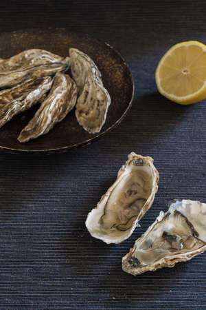 Fresh oysters from the Ebro delta, prepared with natural lemon juice. Oysters closed on a wooden plate on a black background.