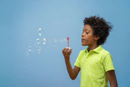 cute mixed race boy blowing soap bubbles dressed in a yellow shirt on blue background