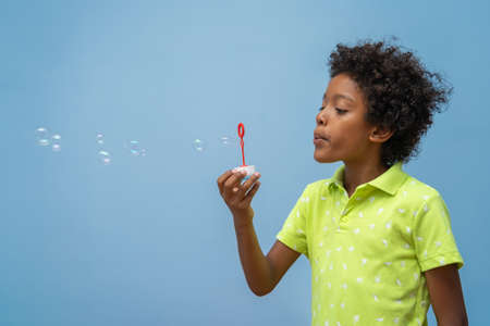 little black boy blowing soap bubbles on blue background, lateral view Stock Photo