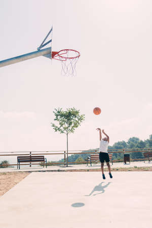 Black boy playing basketball at the park in the morning. Vertical photo Stock Photo