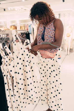 Black woman choosing dress from new collection of clothes in a boutique. Beautiful woman choosing clothes in a clothing shop.