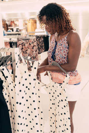 Beautiful black woman shopping for clothes at retail apparel shop in the shopping mall. Modern trade lifestyle.