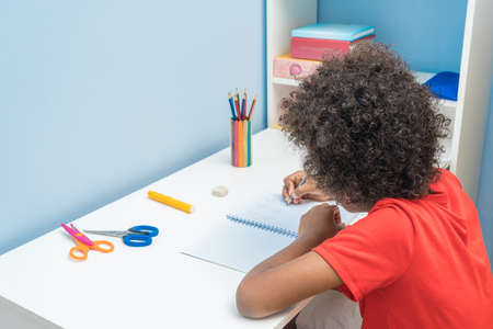 Black boy writing in notebook. Child sitting at the desk home and doing his homework. School, children, education concept Stock Photo