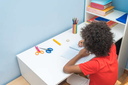 Black boy writing in notebook. Child sitting at the desk home and doing his homework. School, children, education concept. Aerial view