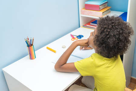 Portrait of pensive black boy doing homework alone at table at home Aerial view