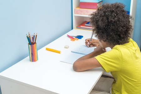 Black boy writing in notebook. Child sitting at the desk home and doing his homework. School, children, education concept Banque d'images