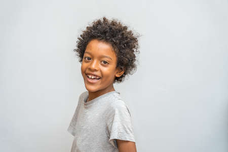 curly-haired black boy laughs out loud. Copy space on gray background