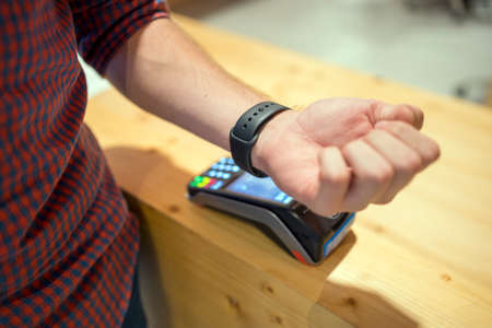 Close-up of a mans arm while making a payment with the smart watch Stock Photo