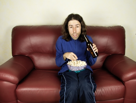 kibitz: a young man look the football on the couch