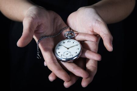 a silver  pocket watch in the black background