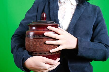 funerary urn and girl in the green screen Stock Photo