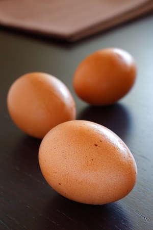 albumen: Fresh hen eggs on a brown wooden table