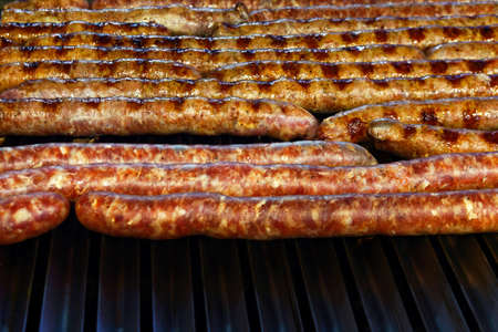 sizzle: Grilled and raw sausages over barbecue lines