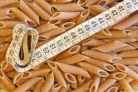 dietetic: Dietetic whole wheat italian pasta penne whit tape meter Stock Photo