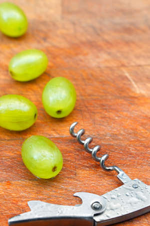 cork screw: Grapes and steel cork screw on wooden table