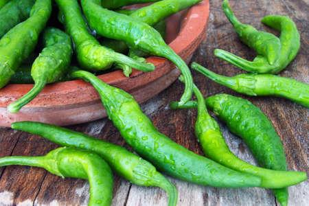 Fresh green italian bell pepper friggitelli in earthenware pot on wooden background Stock Photo