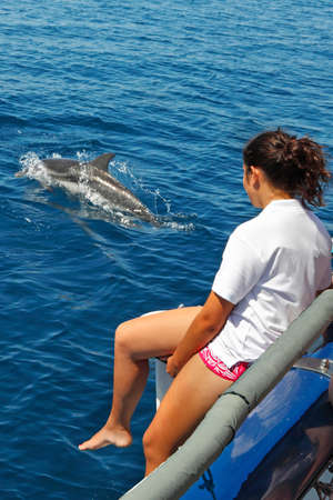 cetaceans: Young tourist girl during a dolphin watching