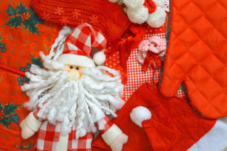 Christmas background with homemade santa claus puppet, hat, red stocking, bake glove and other ornaments Stock Photo