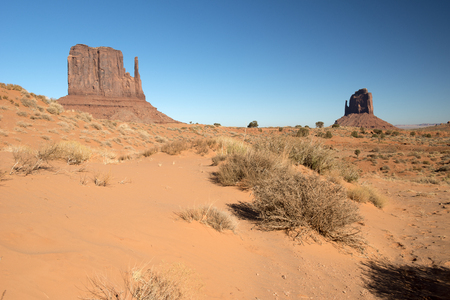 Monument Valley meaning valley of the rocks is a region of the Colorado Plateau characterized by a cluster of vast sandstone buttes, the largest reaching 1,000 ft 300 m above the valley floor. It is located on the Arizona-Utah state line, near the Four Co Stock Photo