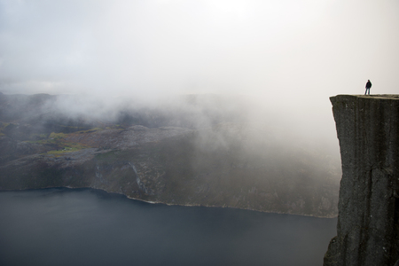 english famous: Preikestolen or Prekestolen, also known by the English translations of Preachers Pulpit or Pulpit Rock, is a famous tourist attraction in Forsand, Ryfylke, Norway. It consists of a steep cliff which rises 604 metres 1982 feet above Lysefjorden, opposite Stock Photo